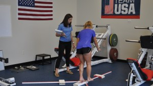 A Physical Therapy student instructs a member of the USA field hockey team