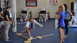 Physical Therapy students assist a member of the National Field Hockey team with an exercise