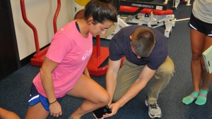 A Physical Therapy student performs a stretch on a field hockey player