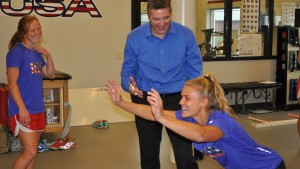 A member of the U.S. National Field Hockey team performs stretches with LVC students